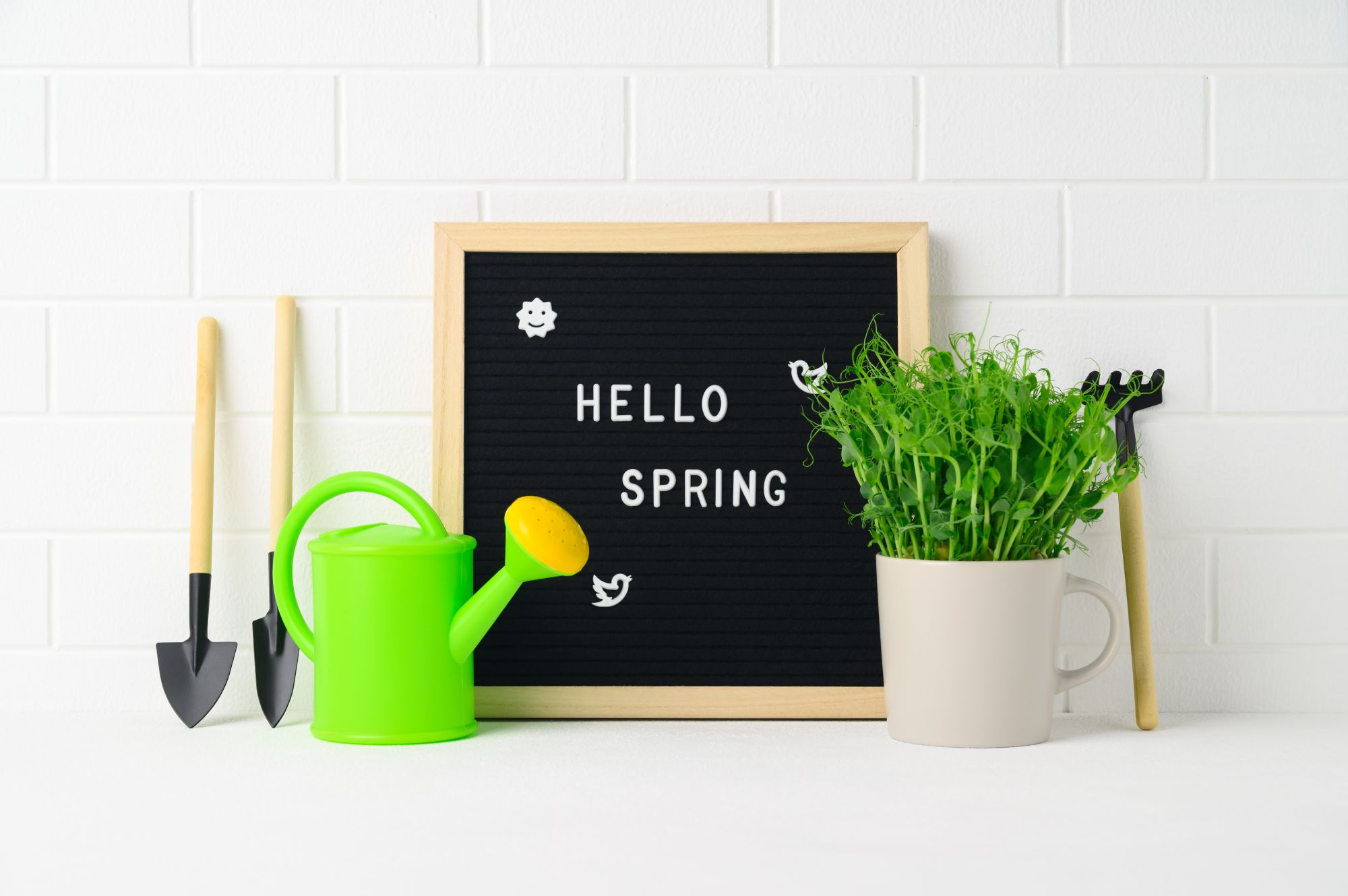 A small letterboard welcoming spring with gardening toys laid out around it
